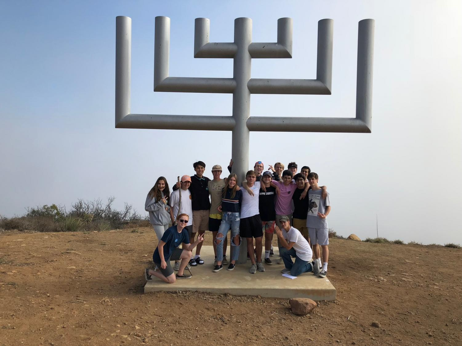 Students gather around the menorah, which stills stands after the campsite burned in Malibu during the Woolsey Fire