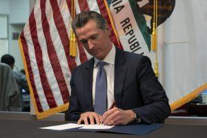 Gov Gavin Newsom signs the Covid-19 response bill.