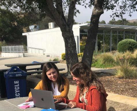 Counselors Julie Ross and Janet Svoboda go on the computer outside the administration building.