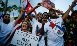 93861712_A-woman-holds-a-placard-reading-Freedom-for-Cuba-as-others-demonstrate-holding-Cuban-and-US-1