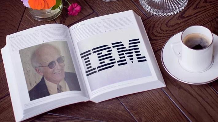 Uma mesa com um livro aberto e uma chícara de café próximo. O livro mostra a foto de Jim Thatcher na página esquerda e o logotipo da IBM na página da direita