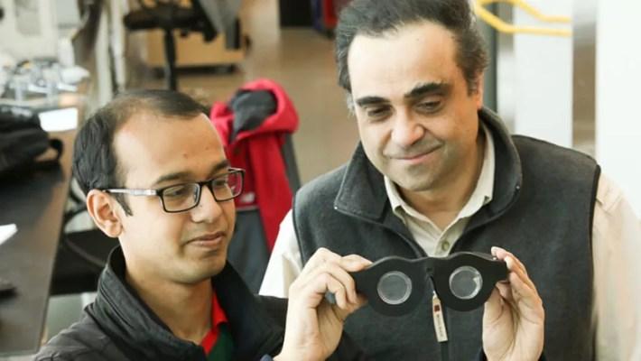 Um estudante de engenharia elétrica e informática na universidade de Utah, nos Estados Unidos, segurando os óculos inteligentes. Ao seu lado o professor Carlos Mastrangelo