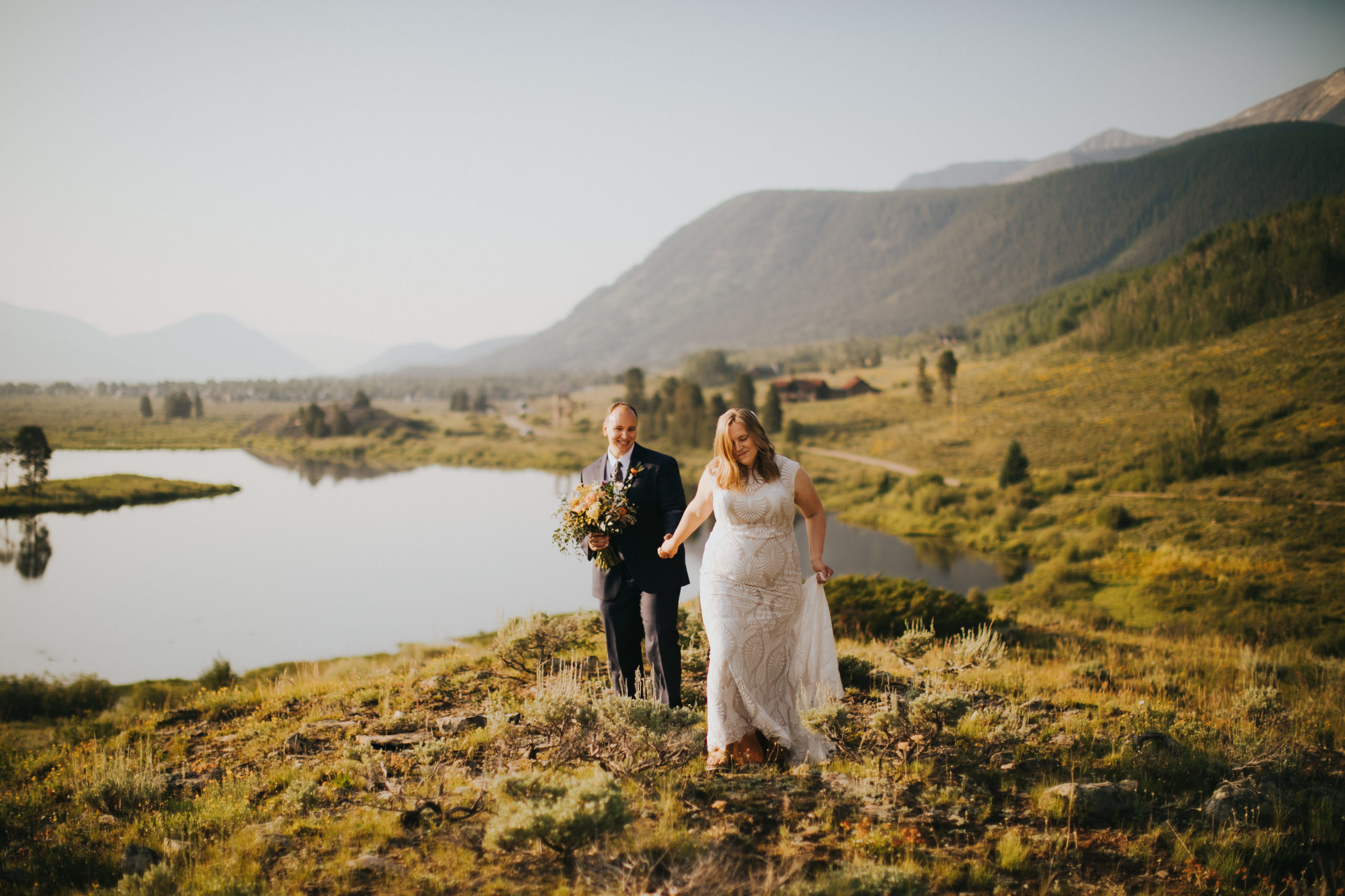 A bride and room walk along a mountainside in Crested Butte, Colorado