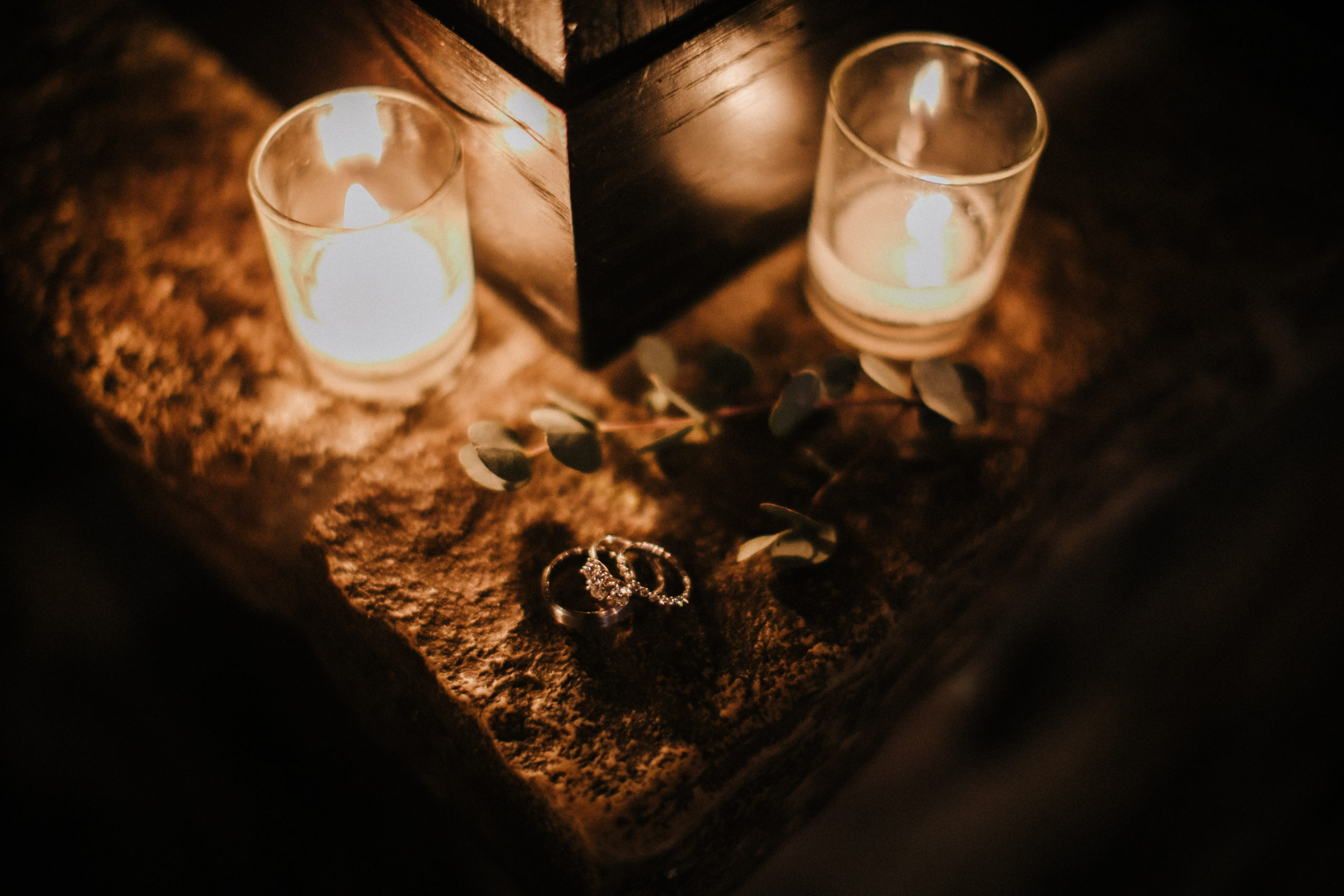 Wedding rings sit on a stone ledge near candlelight