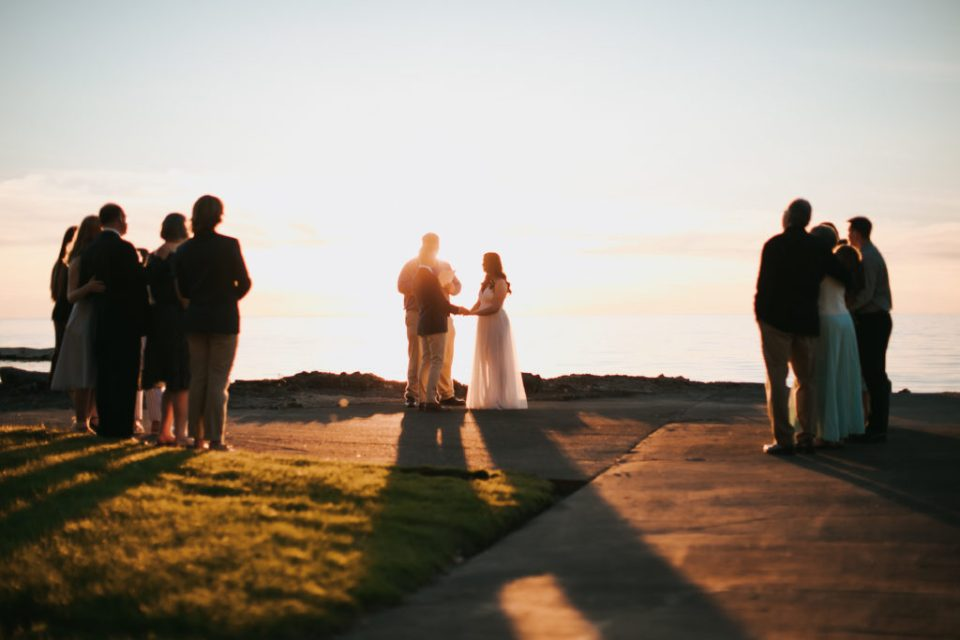 Family surrounds a bride and groom during a sunset wedding ceremony