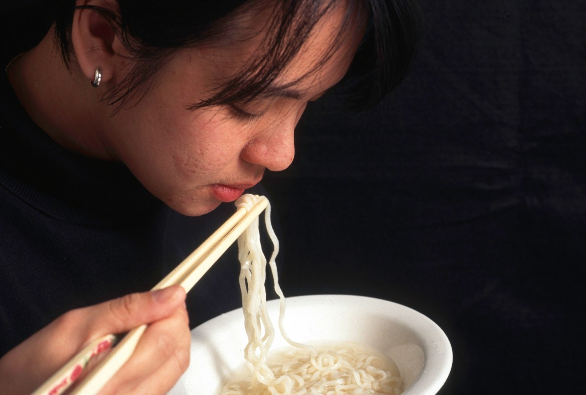 Woman eating Asian noodles with chopsticks.