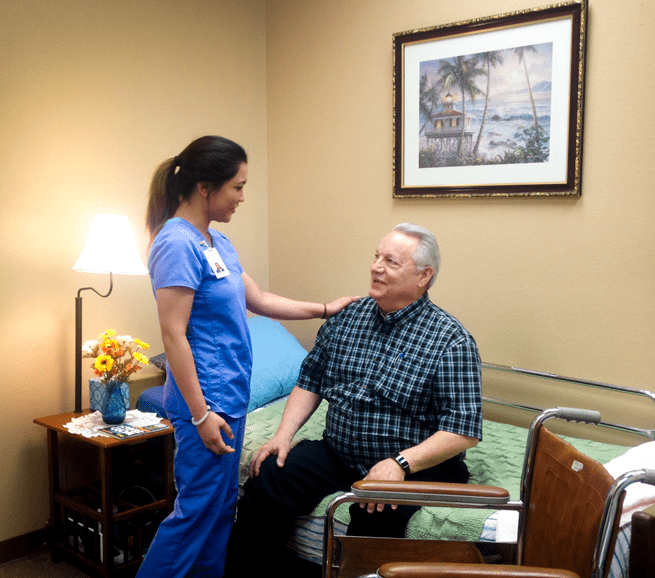Caregiver Reassuring a Senior sitting on a bed