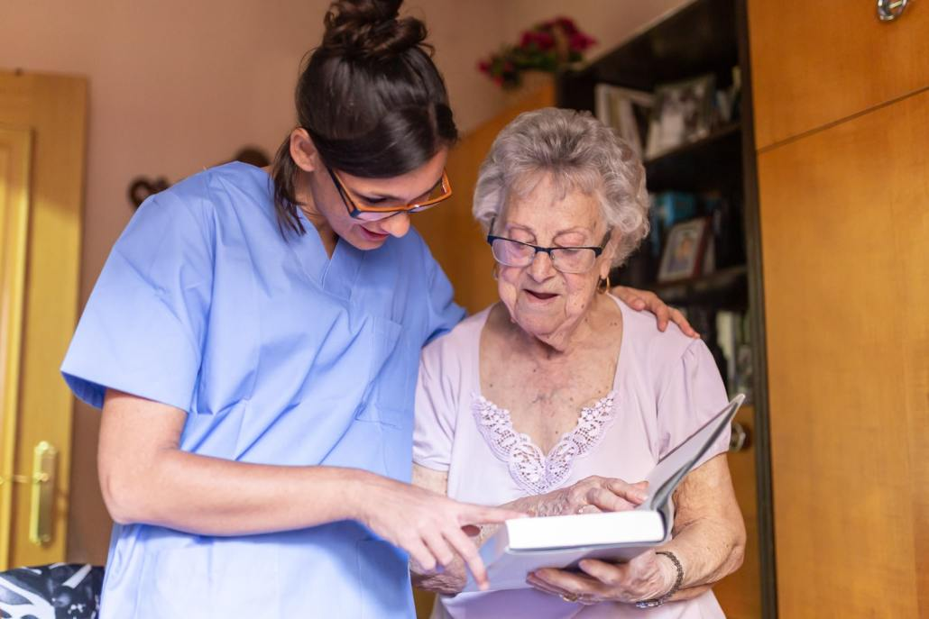 caregiver and senior woman looking at a book