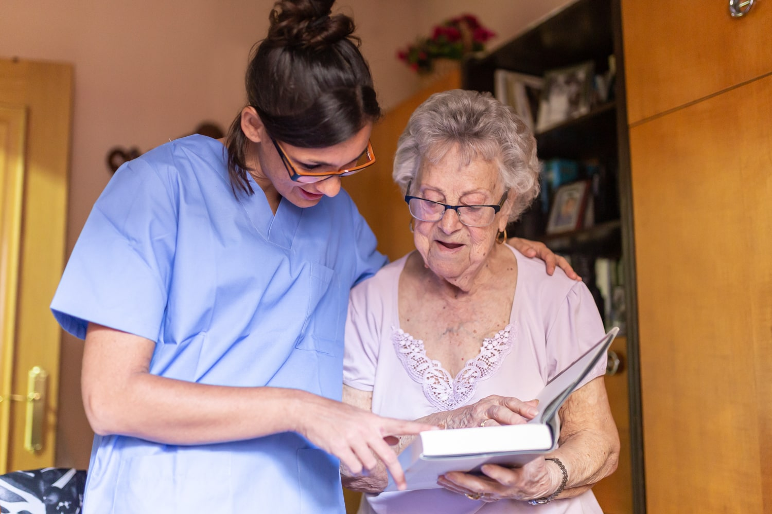 caregiver and senior woman looking at a book