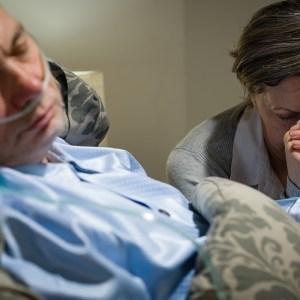 Woman praying for sick man
