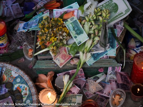 A wish for good health and prosperity, with candles, flowers and pesos
