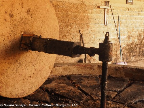 Horse driven stone wheel used to crush roasted agave pineapple