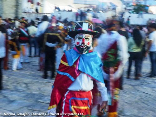 Masked revelers dance in church courtyard and before the altar inside