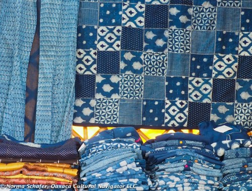Indigo dyed patchwork quilt, with dresses, blouses on table.