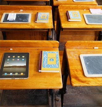 Chalkboards, books, and an iPad sit on wooden desks