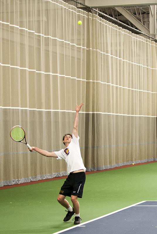 Junior Billy Lennon lofts up the ball as he prepares to serve to his Denison University opponent. The Yeomen were defeated Saturday 4–5 by the visiting Big Red but were able to bounce back Sunday to defeat the New York University BobCats 5–4.
