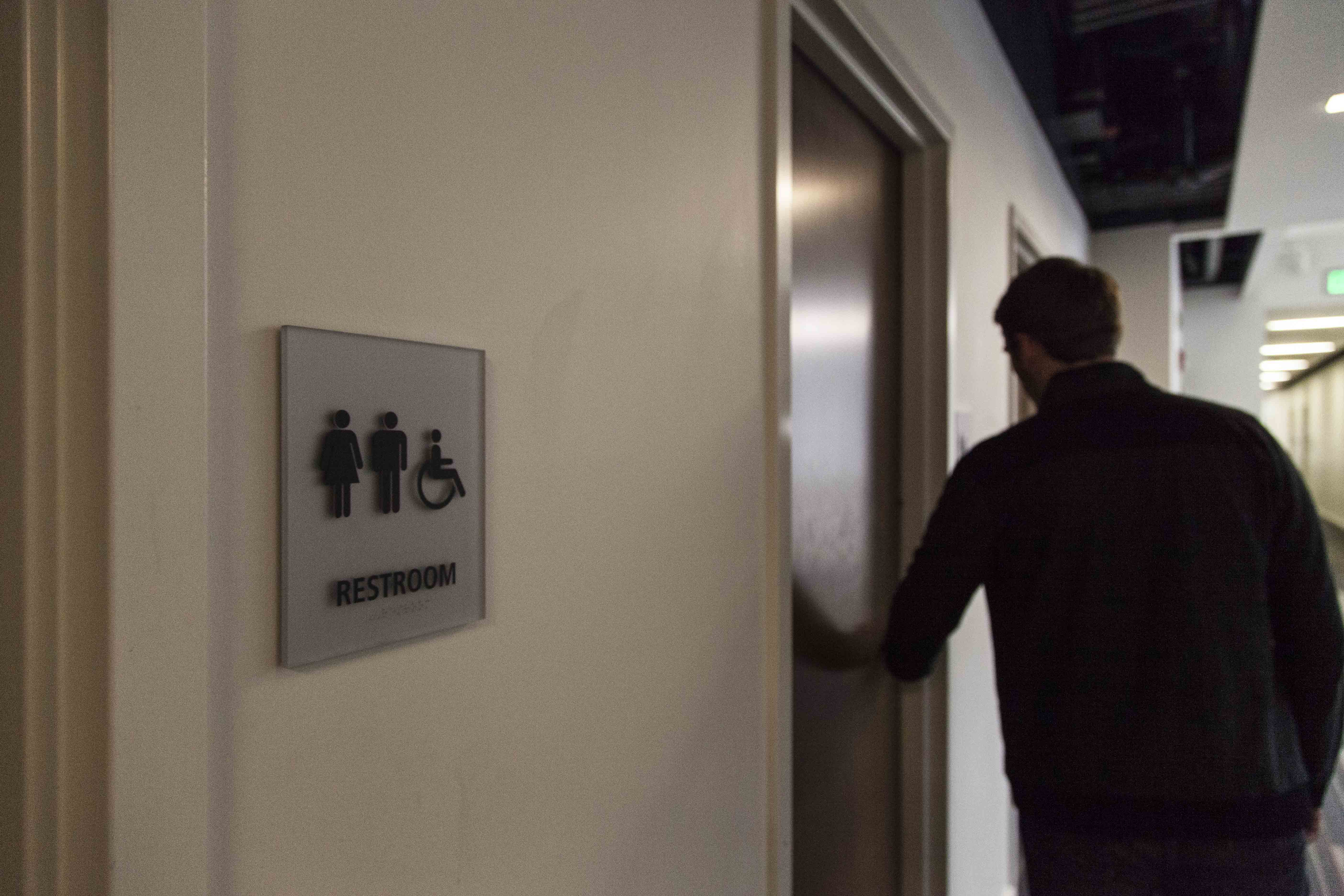 A student walks into a bathroom in the Science Center. Students have recently questioned the lack of gender-neutral restrooms in academic buildings.