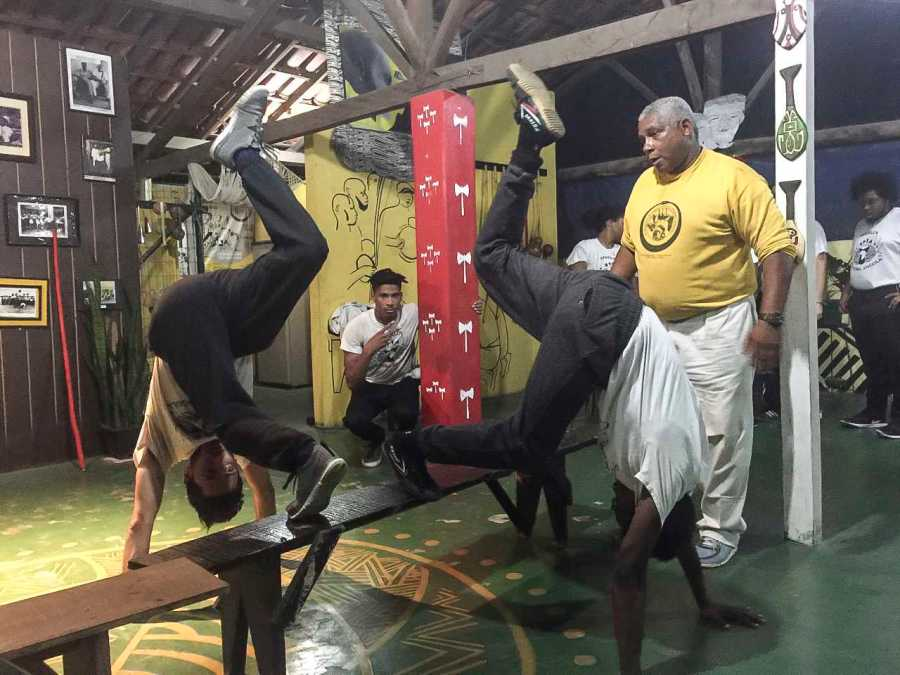 From+left+to+right%2C+College+senior+Dav%C3%ADd+Zager+and+College+junior+Deron+Essex+receive+instruction+in+Capoeira+Angola+from+Mestre+Jurandir+of+the+International+Capoeira+Angola+Foundation.+Capoeira+is+a+martial+art+and+dance+form+developed+by+Angolans+in+Brazil+in+the+16th+century.+The+art+form+is+practiced+in+countries+all+over+the+world%2C+and+made+its+way+to+the+U.S.+in+the+late+20th+century.%C2%A0%0A%0ASeveral+students+took+part+in+the+trip+to+Brazil+over+Winter+Term%2C+led+by+Associate+Professor+of+Theater+and+Africana+Studies+Justin+Emeka%2C+OC+%E2%80%9995.+Students+spent+20+days+in+the+cities+of+Belo+Horizonte+and+Salvador%2C+working+with+three+different+Capoeira+groups+and+participating+in+a+facilitated+discussion+on+how+the+art+can+be+used+to+face+racial+divides+and+inequality+in+the+U.S.%C2%A0