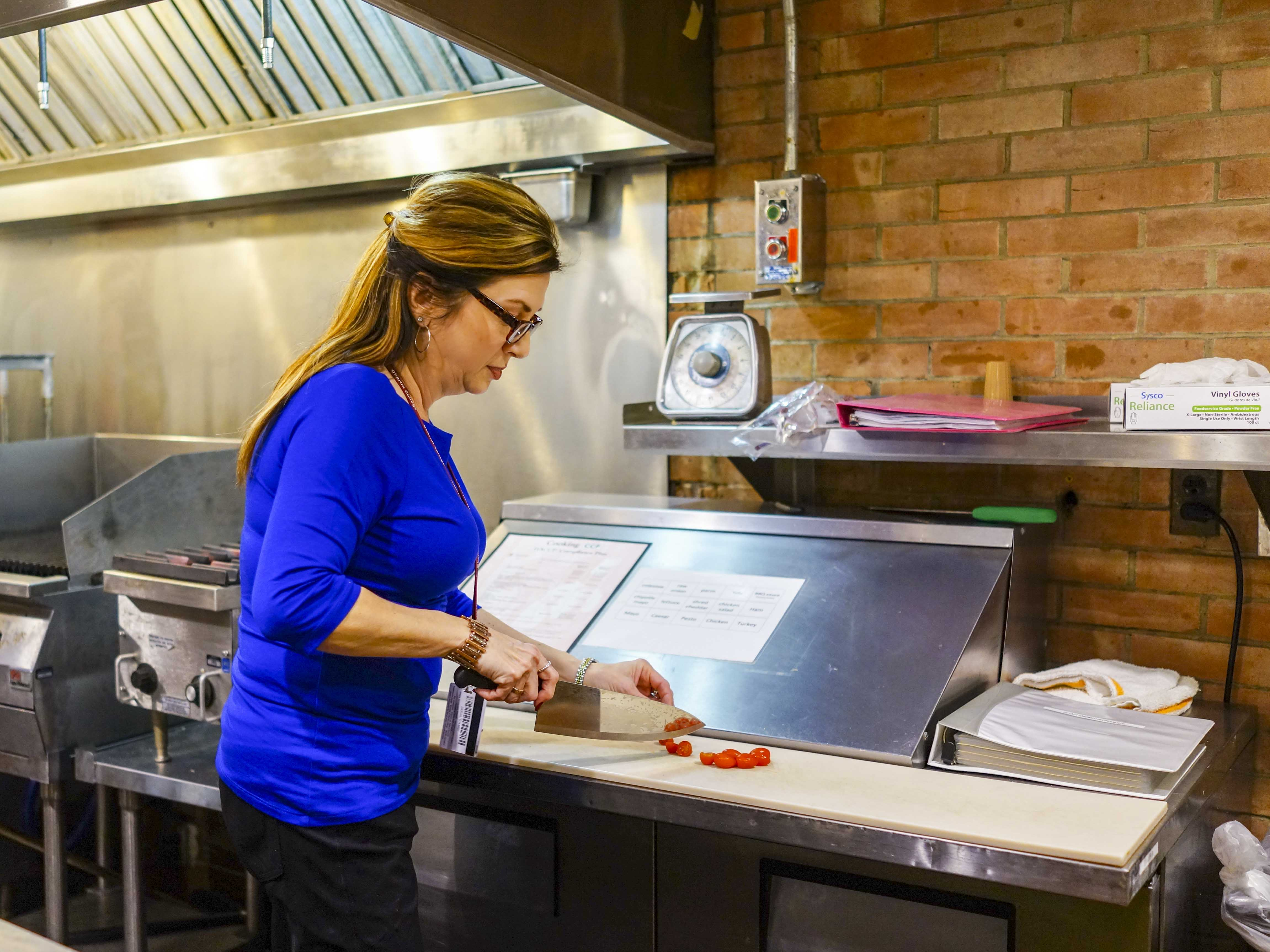 Catering Manager Noreen Vance cuts tomatoes in the Rathskeller for use in DeCafé. The Rathskeller stopped serving food at the beginning of the semester due to spending cuts in Student Life.