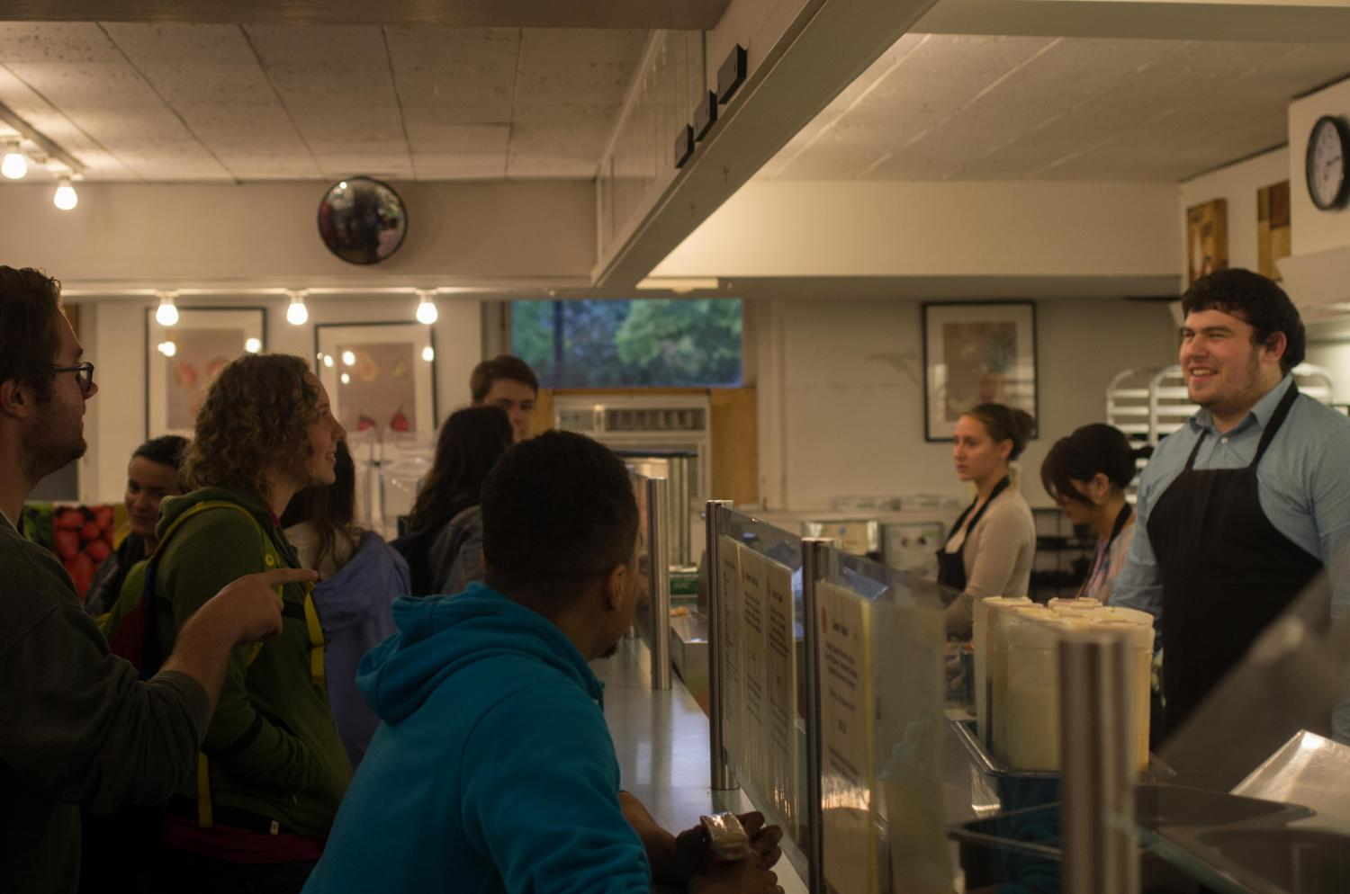 Students stand in a line at DeCafé, where they can now use meal swipes to purchase food.