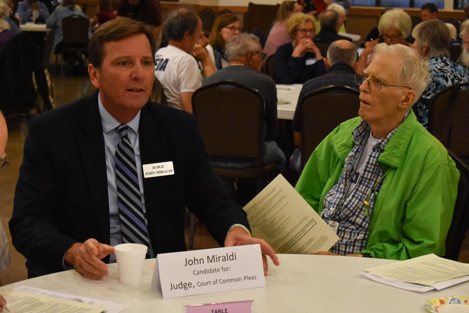 John Miraldi, a judicial candidate, speaks with a community member at Community Candidates Night.