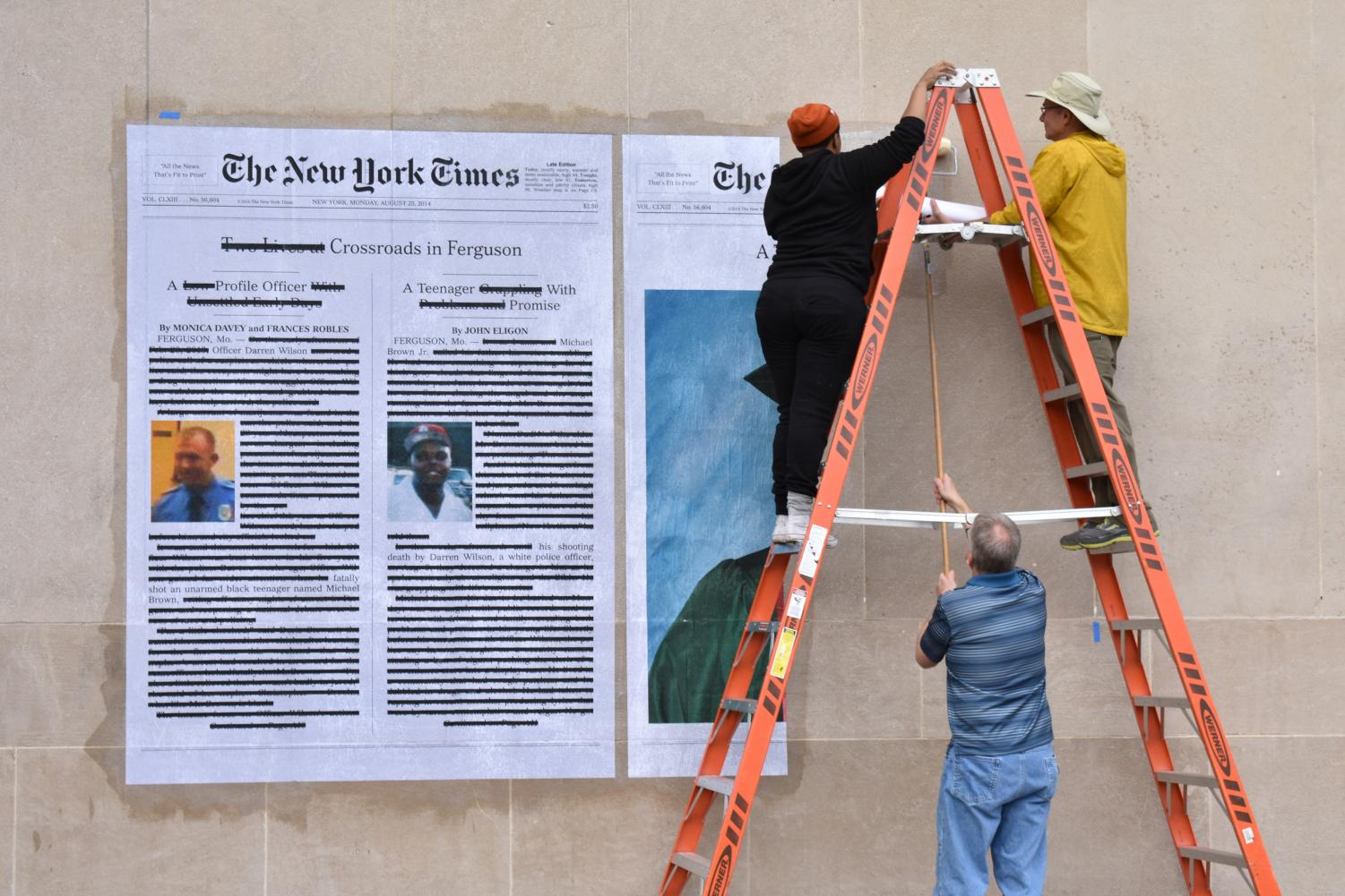 "Alexandra Bell and others install ""A Teenager with Promise"" outside Mudd library on Tuesday, Oct. 30. The work critiques major media coverage of the 2014 fatal shooting of Michael Brown."