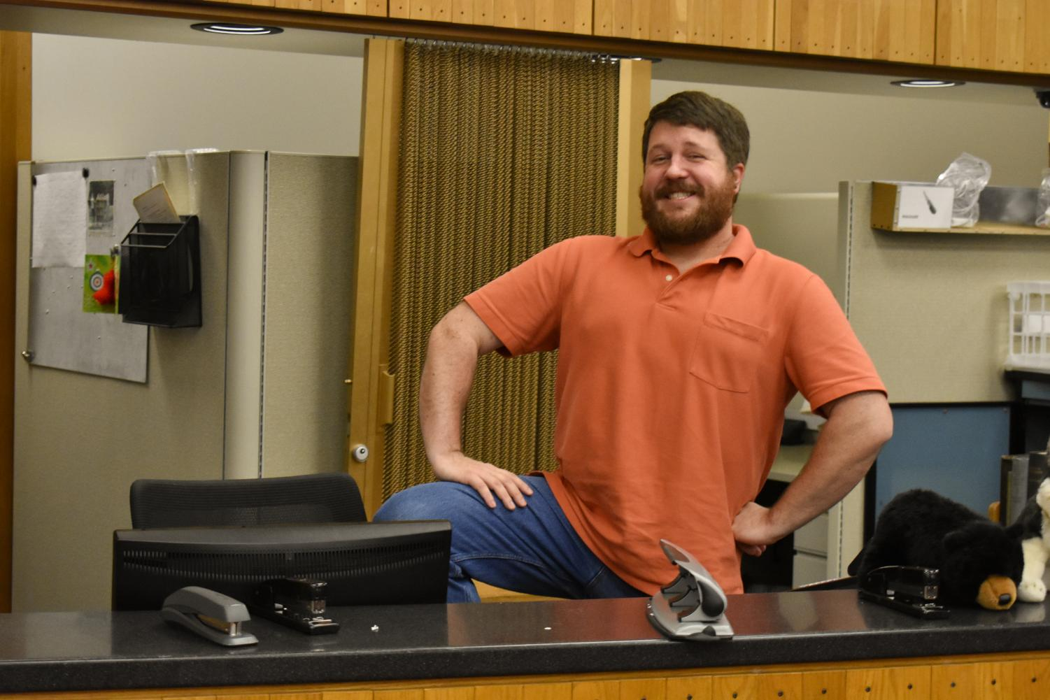 Joseph B. Maiville, OC '07, poses behind the circulation desk in Mudd library.