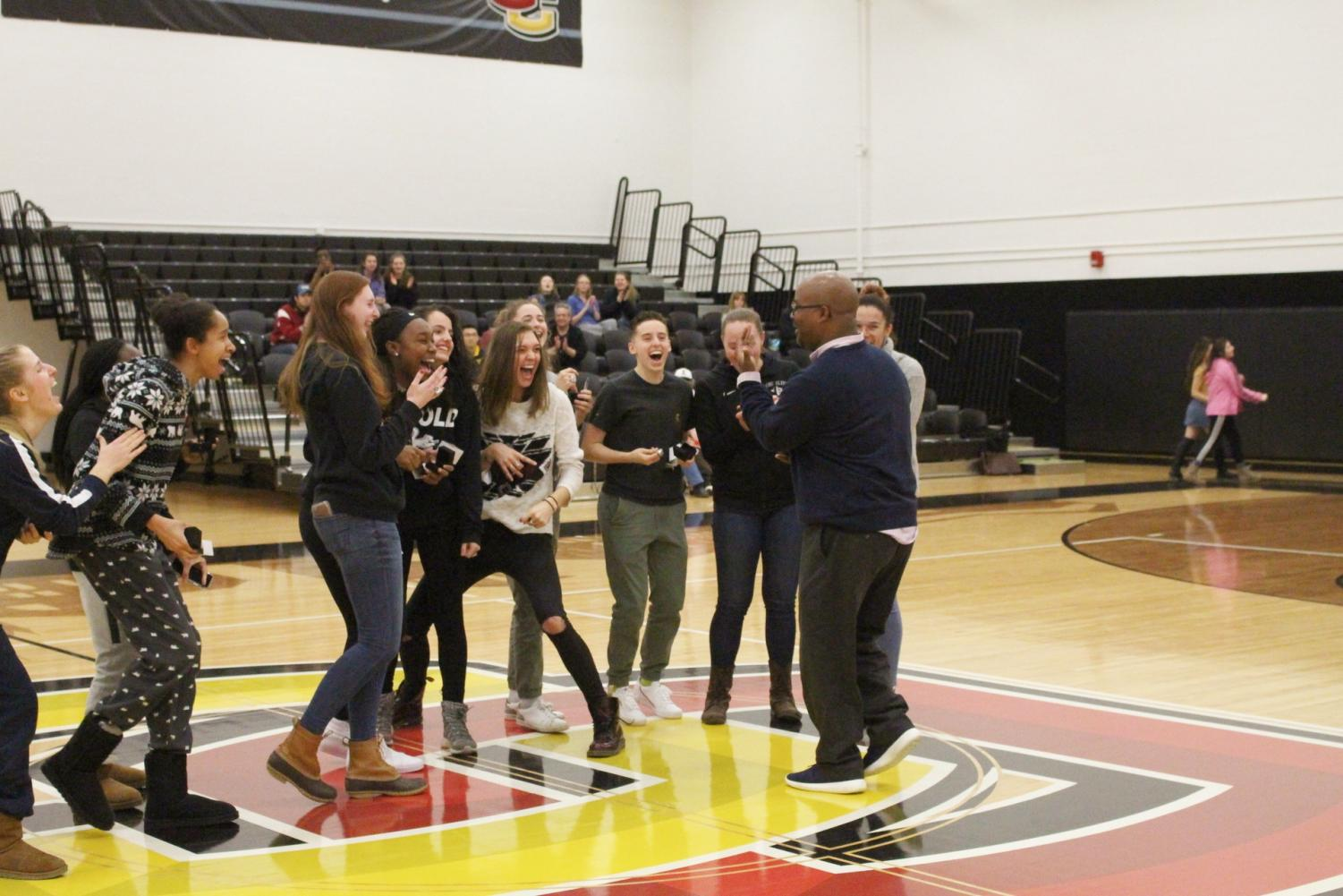 Women's Basketball Head Coach Kerry Jenkins and his players share a laugh at the December ring ceremony celebrating their NCAC championship. Jenkins, who announced his plans to step away from the program a month ago, departs Oberlin as the winningest coach in program history.