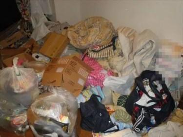 布団、衣類をはじめ床一面に広がる不用品