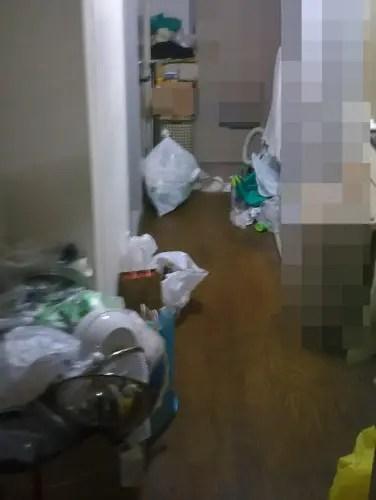 ワンルームの床に散乱する生活ゴミ