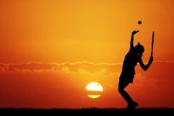 girl playing tennis at sunset