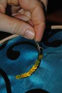 On pique le crochet par dessous,, on descend les fil dessous on met le fil dedans .