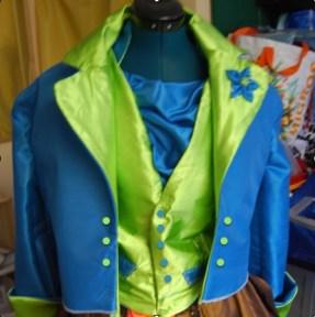 Des bouton turquoises sur le gilet et verts sur la veste qui peut se porter ouverte