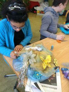 Yasmina poursuit la décoration de son chapeau en utilisant de a peinture paillette