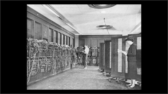 Foto, en blanco y negro, de una pared llena de interruptores y cables
