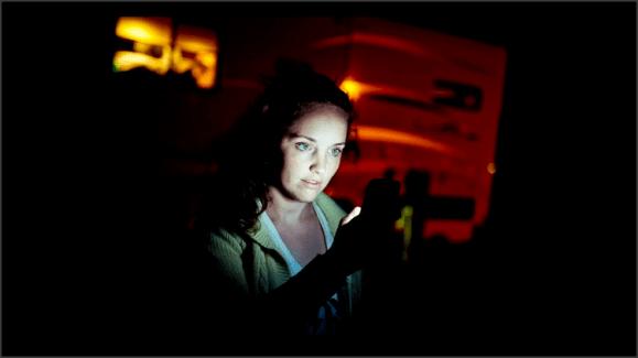 Plano tres cuartos de una mujer, en penumbra, con la cara iluminada por la pantalla del móvil que esrá mirando