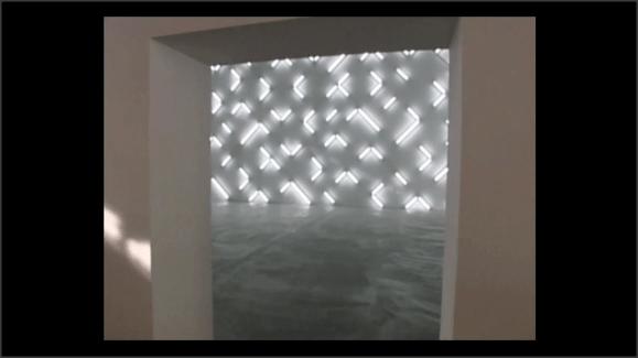 Foto de una instalación artística, vista desde fuera de la sala. Luces de neon dibujan formas sobre una pared de la sala