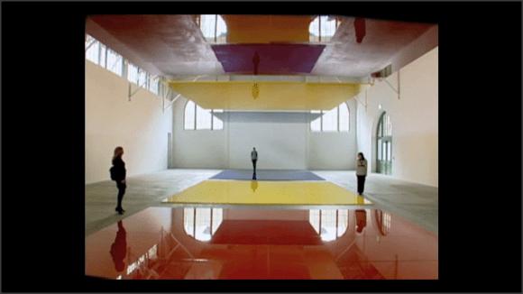 Foto de una instalación. Personas caminan por una enorme sala con enormes placas de color en suelo y techo
