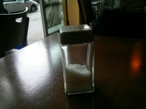 Foto de un salero sobre una foto. Toda la imagen está enfocada, restando importancia al salero, que es el objeto que se quería fotografiar