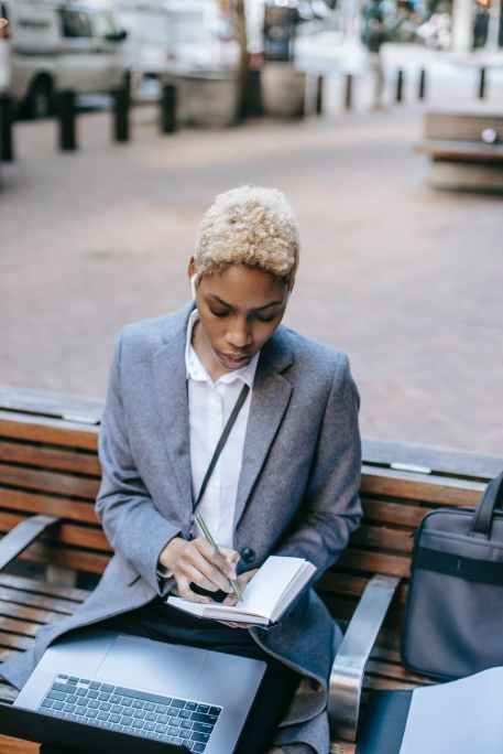 thoughtful businesswoman taking notes in notebook while sitting near city road