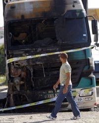 A man walks past a burned truck during a transport strike in Azamabuja north of Lisbon, Portugal