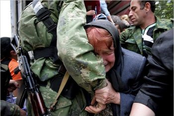 A South Ossetian woman wept as she embraced a Russian soldier in Tskhinvali. Russia's ambassador to NATO asked Monday to meet the alliance's top officials over the crisis in Georgia and rejected any criticism of his country's actions, drawing parallels with NATO's bombing raids in Serbia in 1999.