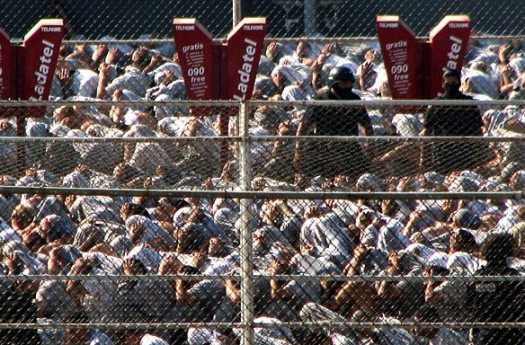 Mexican police officers stand guard over hundreds of inmates after authorities quelled the second riot in days at La Mesa State Penitentiary in Tijuana. The violence broke out over prisoners' allegations of abuse from La Mesa guards. September 17, 2008