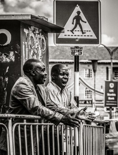 Photograph of two men in the street engaged in a conversation - one yawning.