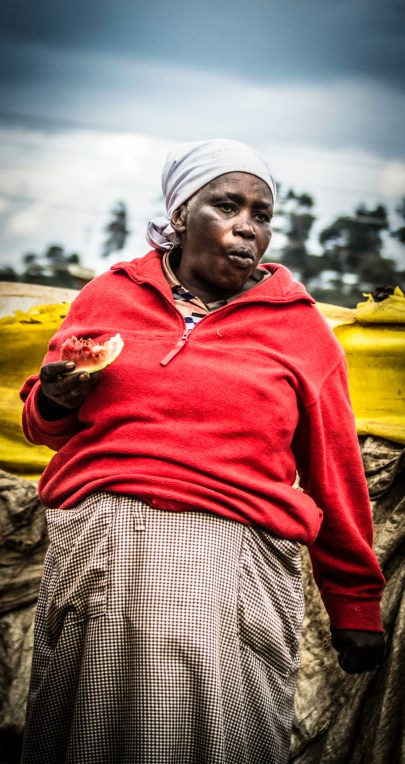 Kenyan woman eating a piece of watermelon