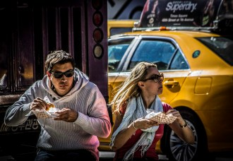 Image of fast-food eating couple, yellow cab in background