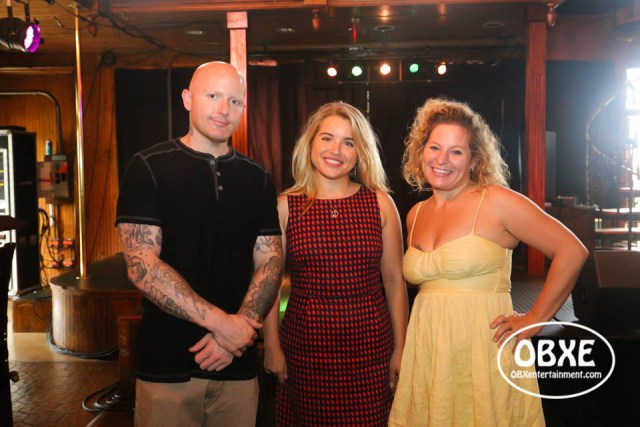 Secret Island Restaurant owners Dru and Natalia Thompson with 'OBXE TV' host Sue Artz, photographed on July 31, 2018 by Matt Artz for OBX Entertainment.