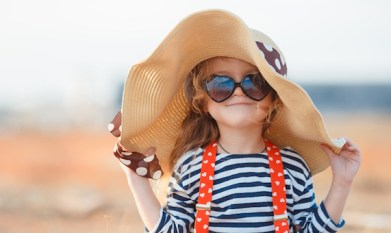 happy little girl in a big hat with sunglasses