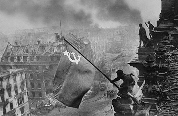 Fig. 3: Yevgeny Khaldei (1945) A soldier raising the Soviet flag over the Reichstag in Berlin