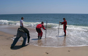 Figure 2. A typical beach survey, using survey rods to record elevations from the dune to the ocean.  Other more sophisticated methods exist.  Photo from University of Rhode Island Geosciences.